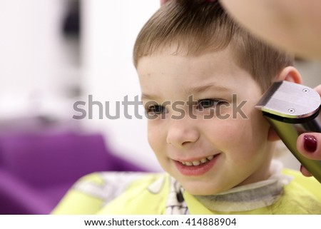 Portrait of happy child at the barbershop - stock photo