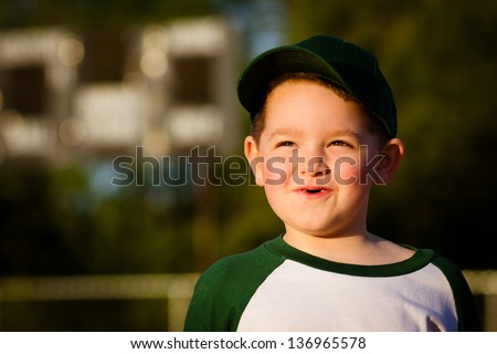 Portrait of happy child baseball player in uniform in front of scoreboard on field - stock photo