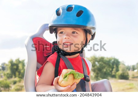 Portrait of happy child (boy) eating lunch (snack) during bicycle ride. Kid has biking helmets. Little toddler  is in the bicycle chair (seat). Caucasian smiling male model. Travel concept.  - stock photo