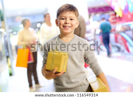 Portrait of happy child holding gift box with his family on background - stock photo