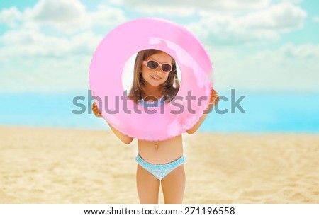 Portrait of happy child with inflatable rubber circle having fun on the beach  - stock photo