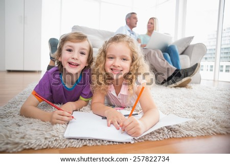 Portrait of happy children drawing on papers while parents sitting on sofa at home - stock photo