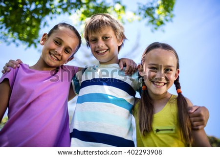 Portrait of happy children standing together in park on a sunny day