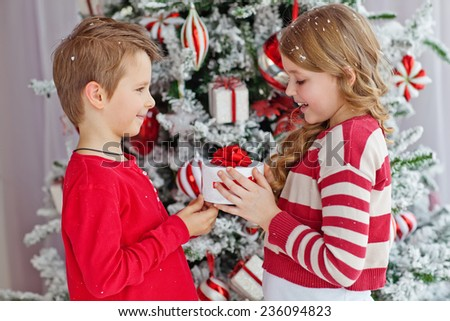 Portrait of happy children with Christmas gift boxes. Two kids having fun at home. Winter holidays concept. High angle view portrait