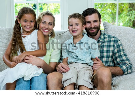 Portrait of happy children with parents sitting on sofa - stock photo