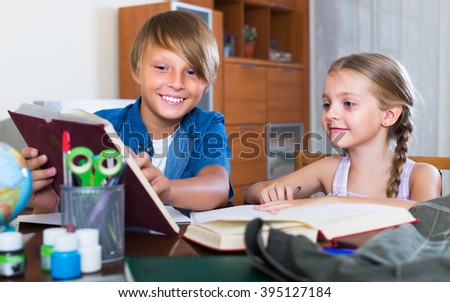Portrait of happy children with textbooks and notes in livingroom