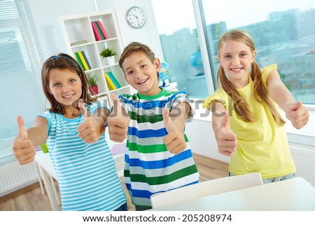 Portrait of happy classmates keeping thumbs up and looking at camera - stock photo