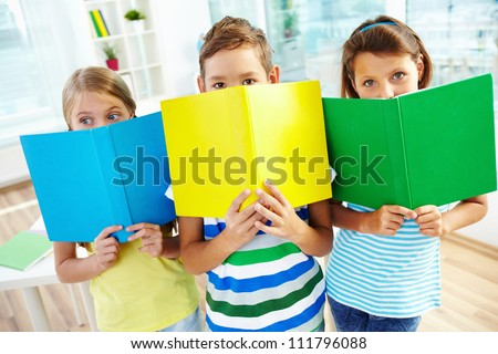 Portrait of happy classmates with books looking at camera in classroom - stock photo