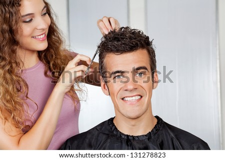 Portrait of happy client getting haircut from female hairdresser at salon