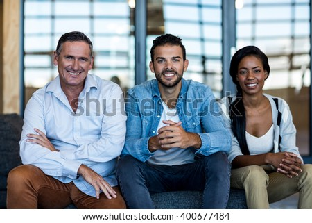 Portrait of happy colleagues smiling at camera in the office - stock photo