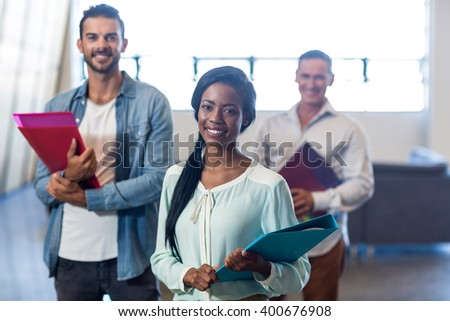 Portrait of happy colleagues with file and folder standing in the office - stock photo
