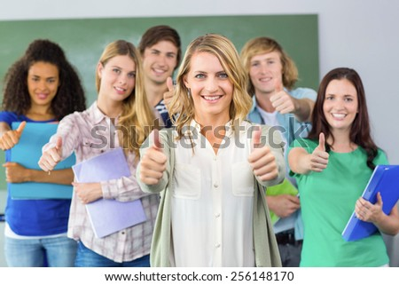 Portrait of happy college students gesturing thumbs up - stock photo