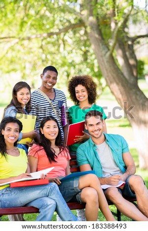 Portrait of happy college students studying on bench at campus