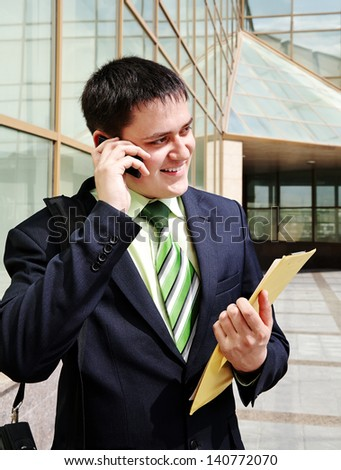 Portrait of happy confident businessman talking by phone near office - stock photo