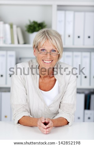 Portrait of happy confident businesswoman at desk in office