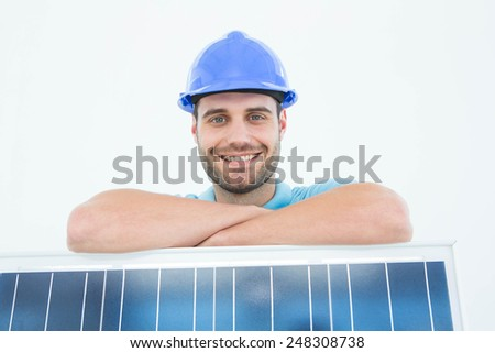 Portrait of happy construction worker leaning on solar panel against white background - stock photo