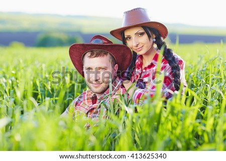 Portrait of happy couple a western style in nature. - stock photo