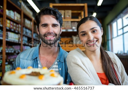 Portrait of happy couple at dessert counter in supermarket
