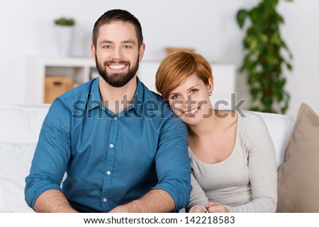 Portrait of happy couple at home, smiling woman leaning on mans shoulder.