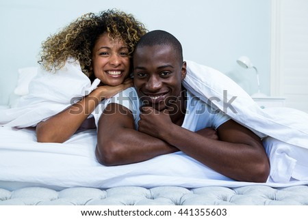 Portrait of happy couple embracing each other on bed in bedroom
