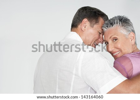 Portrait of happy couple embracing on white background - stock photo