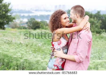 Portrait of happy couple embracing outdoor in park - stock photo