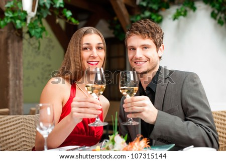 Portrait of happy couple having a drink during their meal - stock photo