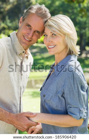 Portrait of happy couple head to head in park