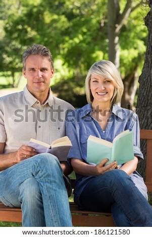 Portrait of happy couple holding books while sitting on bench in park - stock photo