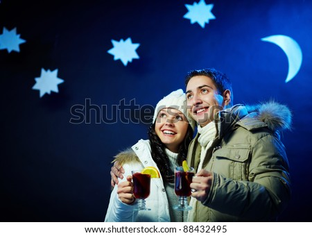 Portrait of happy couple holding glasses of hot tea with moon and stars above their heads - stock photo