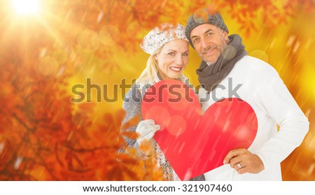 Portrait of happy couple holding heart against walkway along lined trees in the park - stock photo