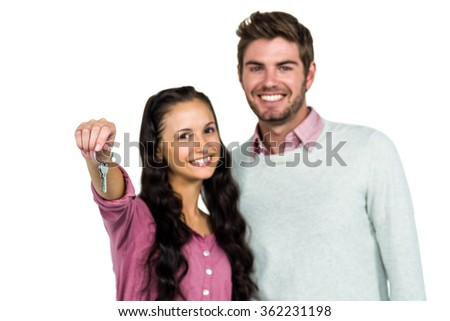 Portrait of happy couple holding keys over white background - stock photo