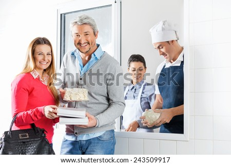 Portrait of happy couple holding pasta packets by chefs discussing at window