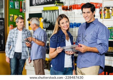 Portrait of happy couple holding tool set in hardware store with customers in background - stock photo