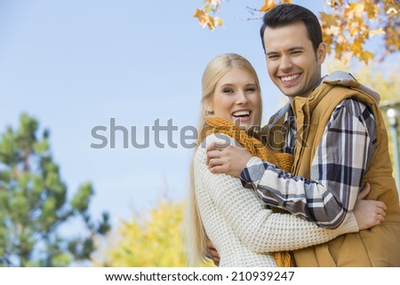 Portrait of happy couple hugging in park