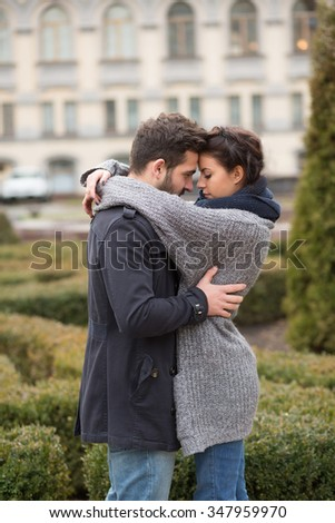 Portrait of happy couple hugging in the autumn park and standing face to face. Beautiful people in love. - stock photo