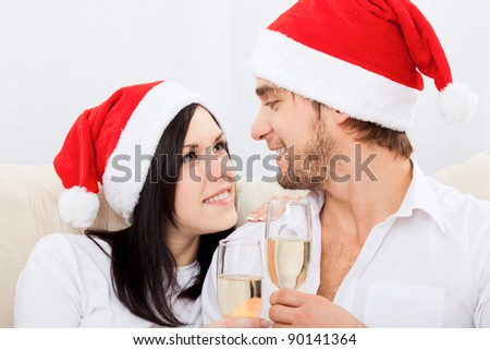 Portrait of happy couple in christmas hats with glass of champagne looking to each other and smiling, sitting indoors at home