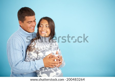 Portrait of happy couple in fashionable pullovers posing against blue background  - stock photo