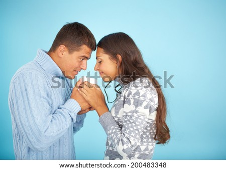 Portrait of happy couple in fashionable pullovers smelling drink in cup  - stock photo