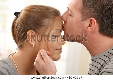 Portrait of happy couple in love, man kissing woman on forehead, stroking face with eyes closed.?