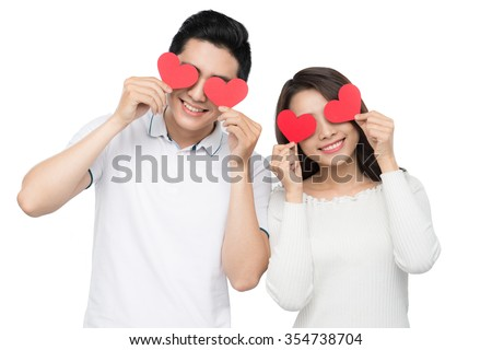 Portrait of happy couple isolated on white background. Attractive man and woman being playful. Attractive young couple holding pink hearts over eyes. - stock photo