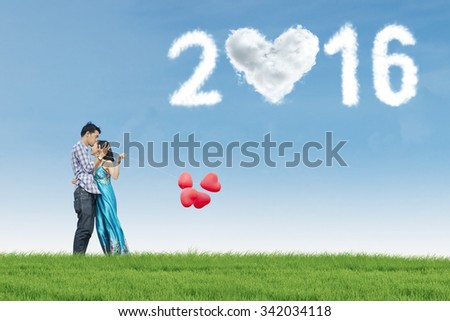 Portrait of happy couple kissing on the meadow while holding balloons under clouds shaped numbers 2016 - stock photo