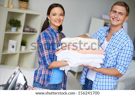 Portrait of happy couple looking at camera while holding stack of towels - stock photo
