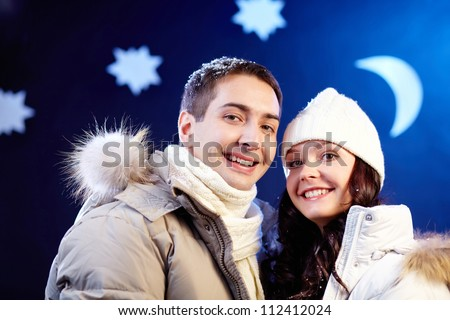 Portrait of happy couple looking at camera with moon and stars above their heads - stock photo