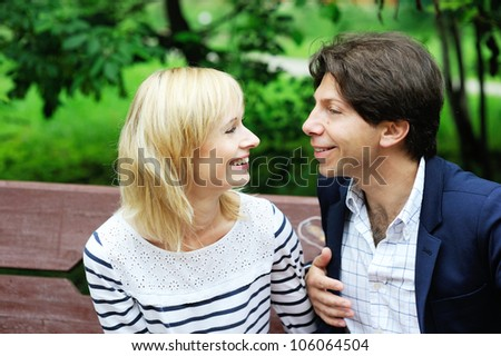 Portrait of happy couple looking at each other while sitting in a park