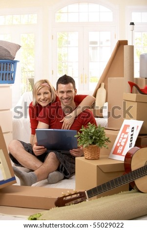 Portrait of happy couple looking at laptop computer together sitting in new house, surrounded with boxes. - stock photo