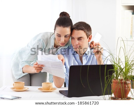 Portrait of happy couple online shopping using laptop and credit card - stock photo