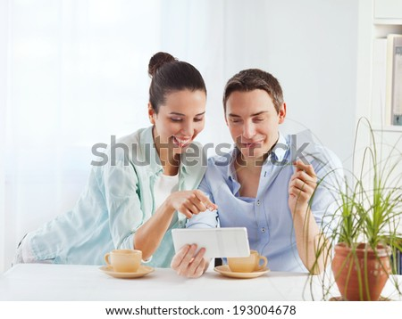 Portrait of happy couple shopping online using digital tablet