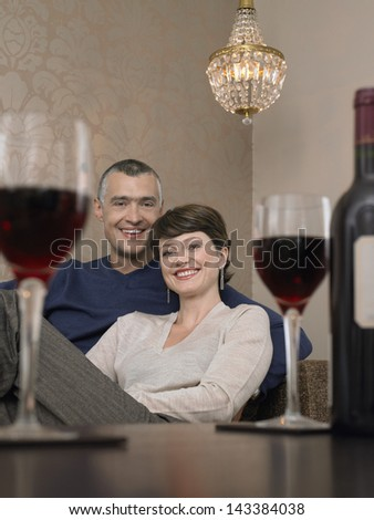 Portrait of happy couple sitting on sofa in front of wineglasses on table
