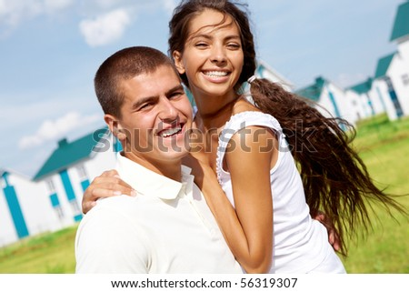Portrait of happy couple smiling at camera while embracing outdoors